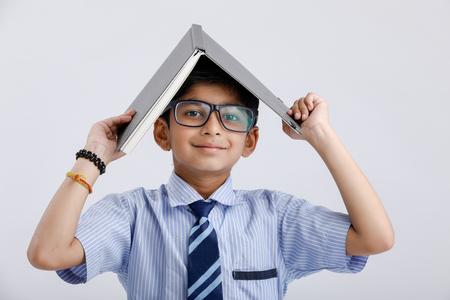 Cute little school boy indio / asiático con gafas con libro en la cabeza.