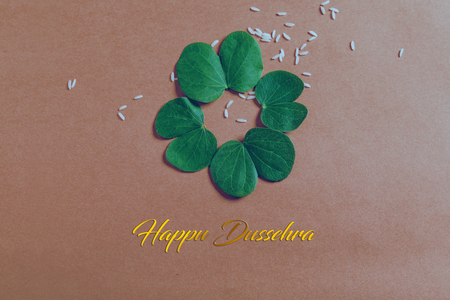 Happy Dussehra greeting card , green leaf and rice