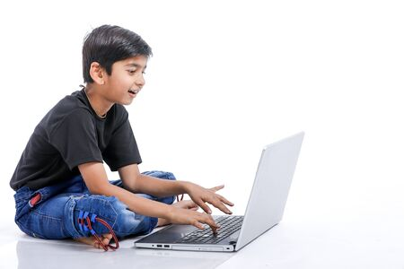 Cute little Indian/Asian boy studying or playing game with laptop computer 写真素材
