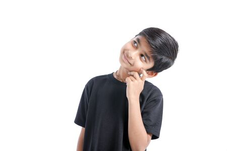 Cute Indian boy thinking idea and looking at up, isolated on white background Imagens