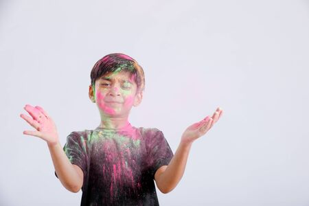 Indian little boy playing with the color and giving multiple expressions in holi festival