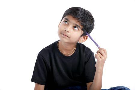 Lindo niño indio pensando en la idea y mirando hacia arriba, aislado sobre fondo blanco.