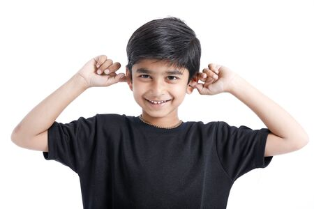 Indian little boy over isolated white background , covering ears with hands.