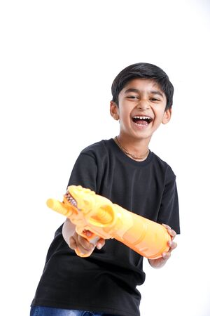 Indian Child playing holi with color gun