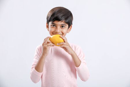 Cute indian/Asian little boy eating Mango with multiple expressions. isolated over white background Banco de Imagens