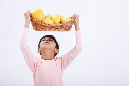 Cute indianAsian little boy holding Mango basket in hand and giving multiple expressions. isolated over white background