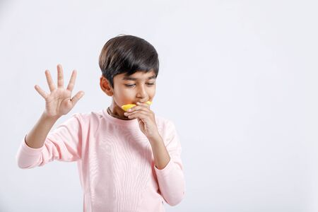 Cute indianAsian little boy eating Mango with multiple expressions. isolated over white background Stock Photo