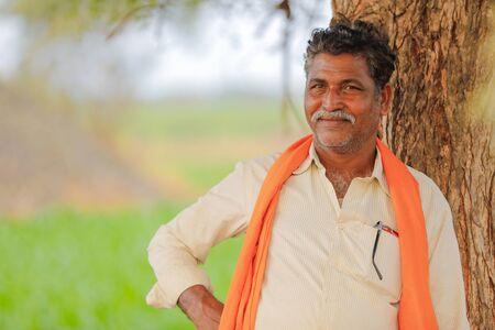 Indian farmer at green corn field Stock Photo
