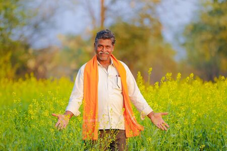 Indian farmer at black mustard  field Stock Photo