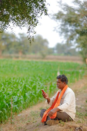Indian farmer using mobile phone at corn field Banco de Imagens - 124974906