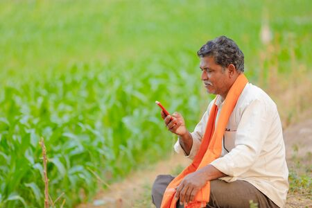 Indian farmer using mobile phone at corn field