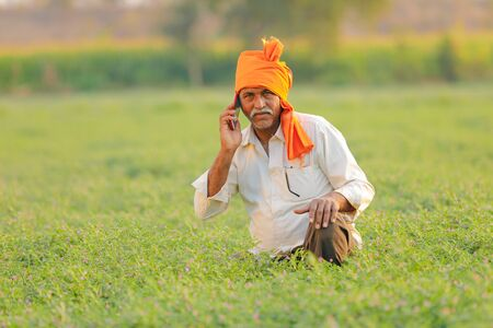 Indian farmer using mobile phone at chickpea field Stock Photo - 124975052