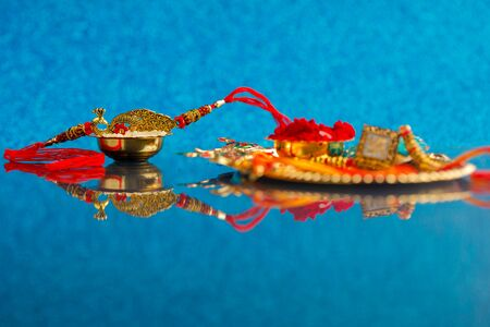 Indian festival Raksha Bandhan , Rakhi with rice grains, kumkum on Decorative plate , A traditional Indian wrist band which is a symbol of love between Brothers and Sisters