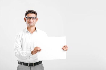Joven ejecutivo de negocios indio mostrando letrero en blanco sobre fondo blanco. Foto de archivo