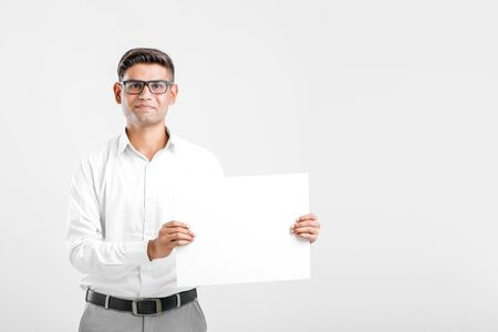 Young Indian business executive showing blank sign board over white background Imagens