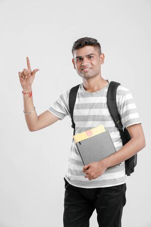 Indian college boy with Holding bag,books and showing direction Stock Photo