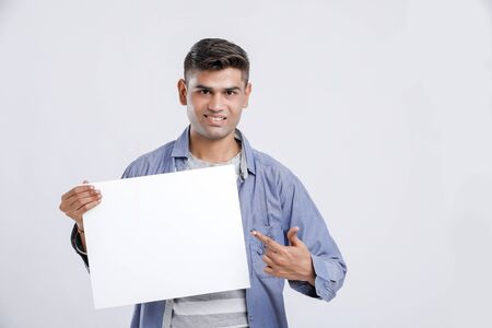 Young Indian College Student showing blank sign board over white background
