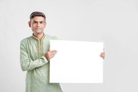 Joven en ropa étnica y mostrando el letrero en blanco
