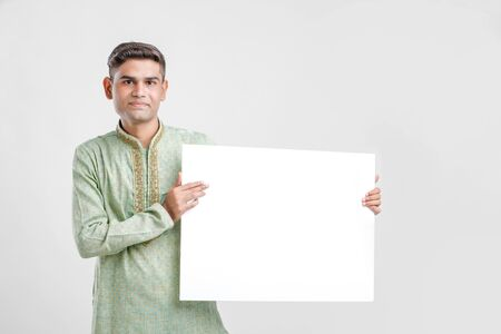 Young man in ethnic wear and showing blank sign board