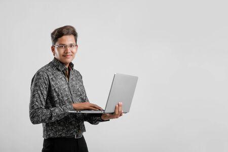 Apuesto estudiante indio / asiático usando laptop