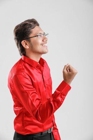 Joven indio / asiático muy feliz y emocionado haciendo gesto de ganador con los brazos levantados