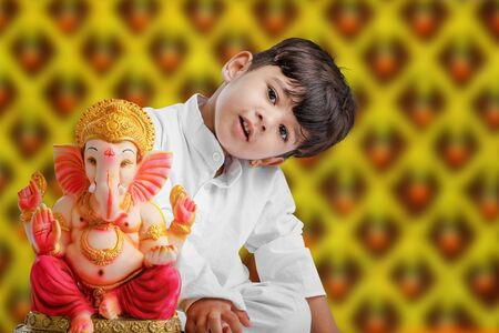 Little Indian boy with lord ganesha , Celebrating Ganesh Festival