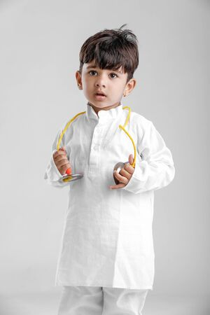 Indian Little Boy in Traditional Dress and learning Musical instrument Stock Photo