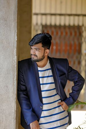 Portrait of a young Indian successful businessman wearing suit over wall background Archivio Fotografico