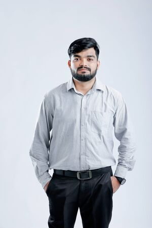 Young Indian Handsome man standing over white background Banco de Imagens