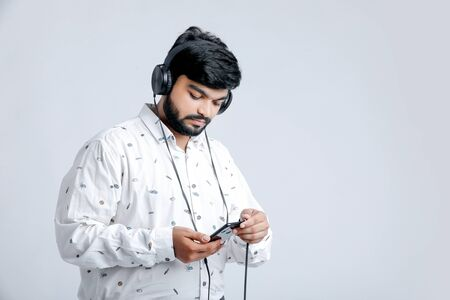 Young Indian man listening music with headphones