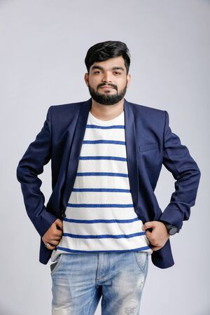 Portrait of a young Indian successful businessman wearing suit over white background