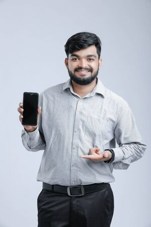 Young Indian man showing mobile screen 写真素材
