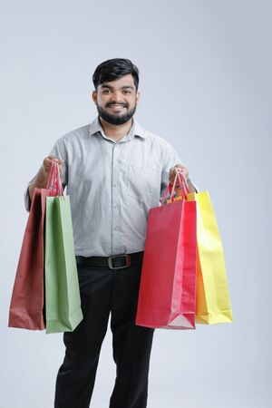 Handsome man holding shopping bags.