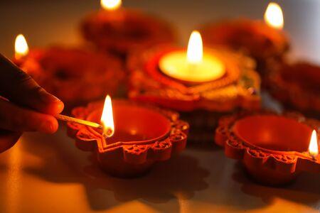 Diwali o festivo de luces. Festival tradicional de diwali indio, manos de mujer sosteniendo lámpara de aceite, con fondo claro de desenfoque. Foto de archivo