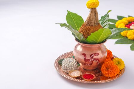 Copper Kalash with coconut , leaf and floral decoration on a white background. essential in hindu puja. 免版税图像