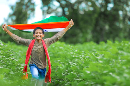 Indian child celebrating Independence or Republic day, Cute little Indian child holding, waving or running with Tricolour flag with greenery in the background,