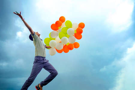 little indian school boy Jumping in sky with tri color balloons and celebrating Independence or Republic day of India Stock fotó