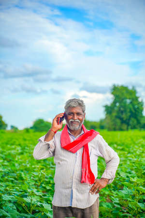 Indian farmer talking on mobile phone at Agriculture field Stock Photo