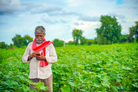 Indian farmer using mobile phone at Agriculture field