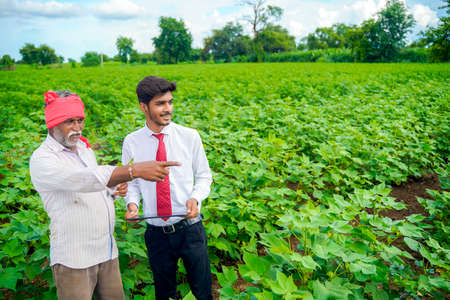 Indian farmer with agronomist at Cotton field , showing some information on tab