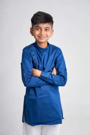Cute indian little boy in ethnic wear and showing expression over white background