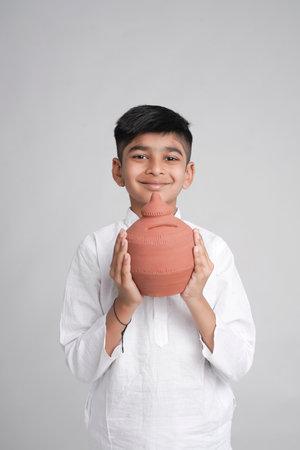 little boy holding clay piggy bank