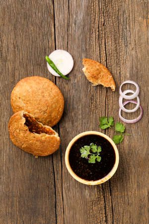 Kachori, green chilly and onion slice on wooden background. kachori is a spicy snack from India also spelled as kachauri and kachodi. Stock Photo