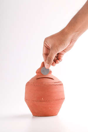 putting a coin into a clay money box: investments, retirement fund and banking concept