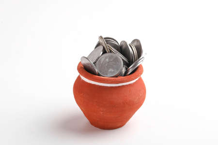 Clay piggy bank pot filled with Indian rupees coin over white background. saving concept