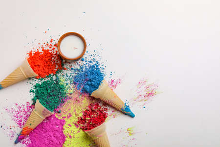 Happy Holi greeting card designed showing Indian traditional sweet drink, powder colors arranged over white background or clay.