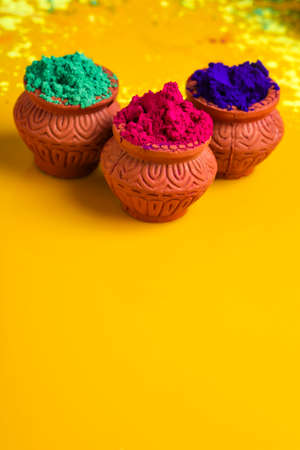 Indian Festival Holi, Multicolor's wooden bowl on yellow background Stock Photo