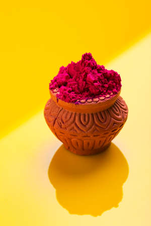Indian festival holi : Red color in wooden clay bowl Stock Photo