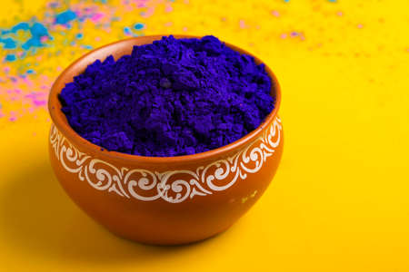 Blue holi powder in bowl isolated on yellow background Stock Photo