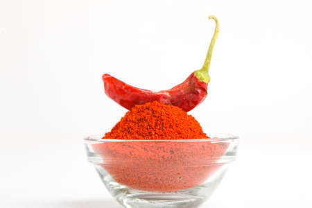 Dried red chilli and powder in glass bowl on white background.